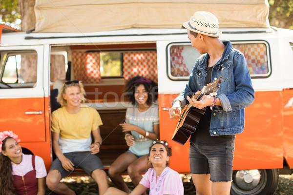 Friends looking at man playing guitar Stock photo © wavebreak_media