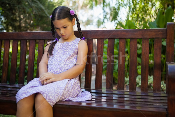 Stock photo: Upset girl looking down while sitting on wooden bench