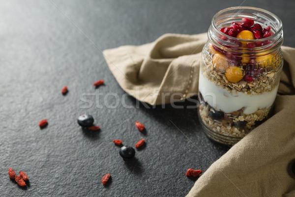Yogurt with pomegranates and golden berries in glass jar Stock photo © wavebreak_media