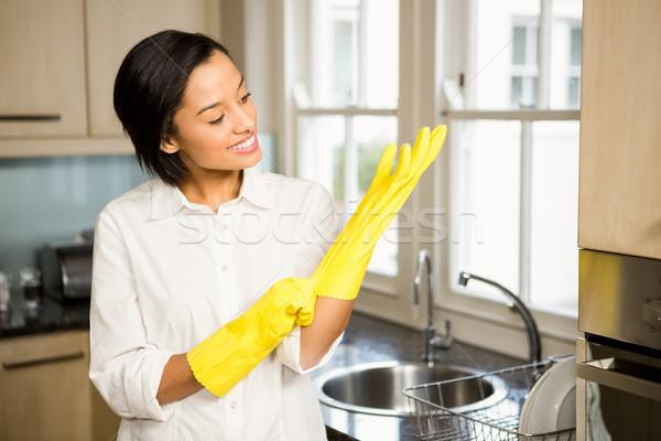 Lächelnd Brünette tragen gelb Handschuhe Küche Stock foto © wavebreak_media