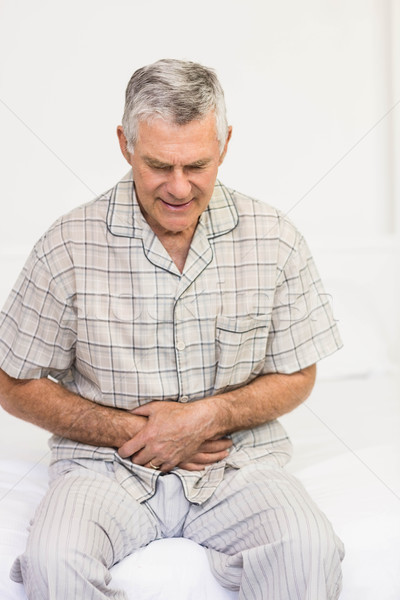 Stock photo: Suffering senior man holding his belly