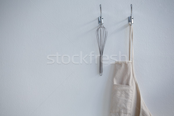 Apron and whisker hanging on hook Stock photo © wavebreak_media