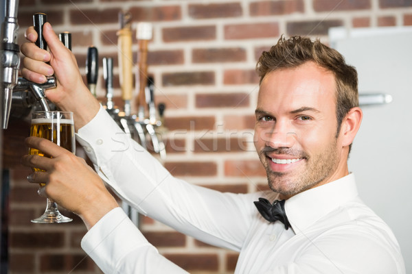 Handsome barman pouring a pint of beer Stock photo © wavebreak_media