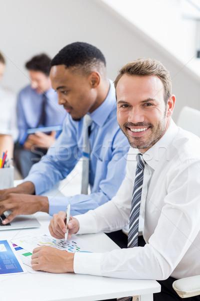 Businessman reviewing a statistical report at desk Stock photo © wavebreak_media