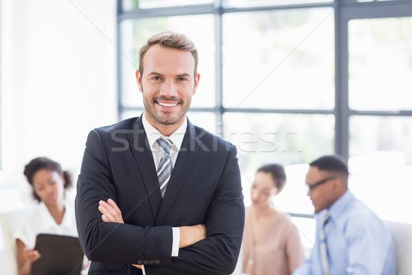 Happy businessman standing with arms crossed Stock photo © wavebreak_media