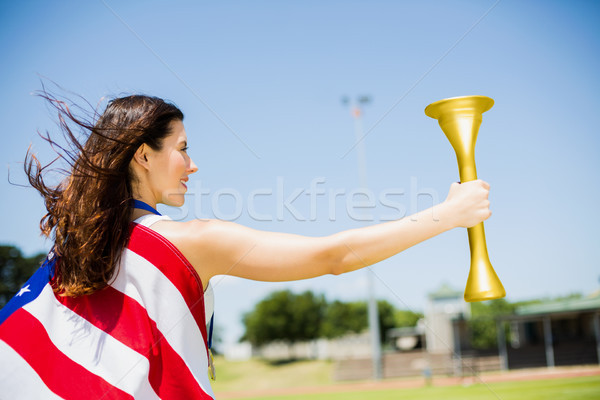 Female athlete wrapped in american flag holding fire torch Stock photo © wavebreak_media