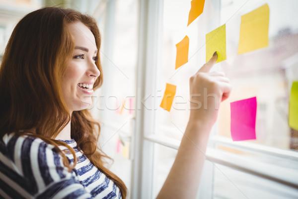 Mutlu işkadını dokunmak yapışkan notlar pencere Stok fotoğraf © wavebreak_media