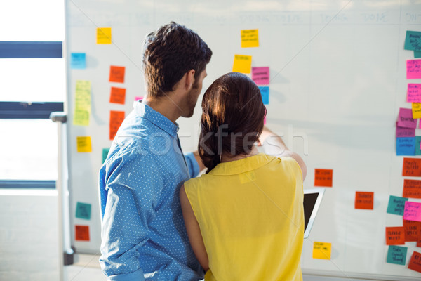 Business executive and co-worker looking at sticky notes on whit Stock photo © wavebreak_media