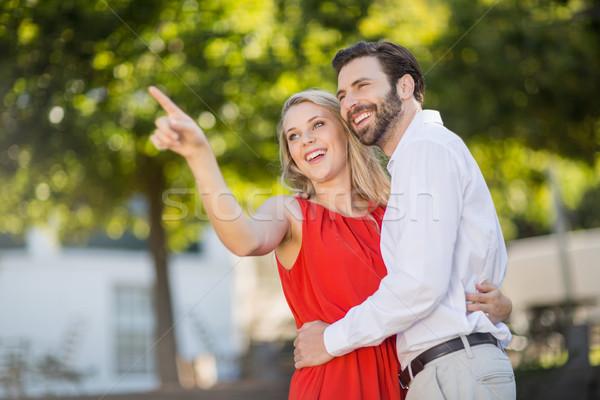 Femme pointant distance parc sourire homme Photo stock © wavebreak_media
