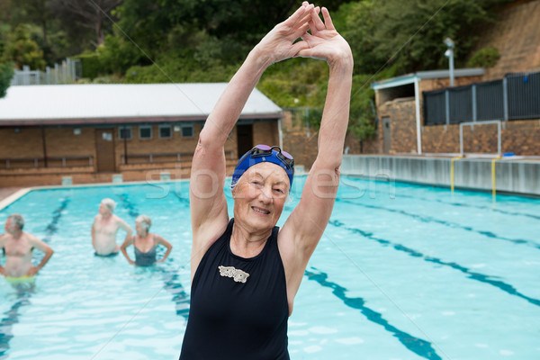 Smiling senior woman excerising at poolside Stock photo © wavebreak_media