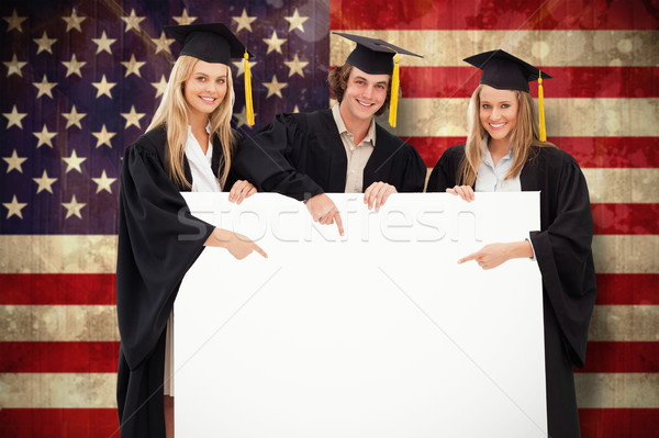 Composite image of three students in graduate robe holding and p Stock photo © wavebreak_media