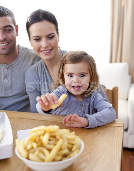 Little girl eating fries at home Stock photo © wavebreak_media