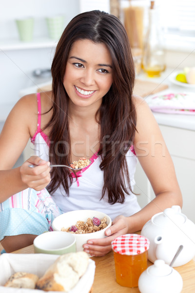 Smiling woman eating muesli with fruits sitting in the kitchen Stock photo © wavebreak_media