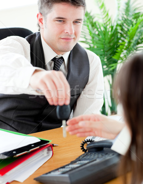Stock photo: Charming salesman giving car's key to his customer  sitting in his office