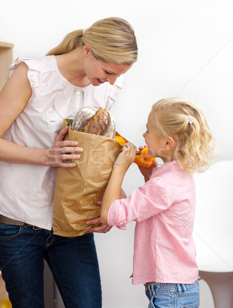 Little girl unpacking grocery bag with her mother Stock photo © wavebreak_media