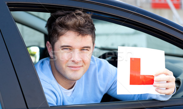 Positvie young male driver holding a L sign sitting in his car  Stock photo © wavebreak_media