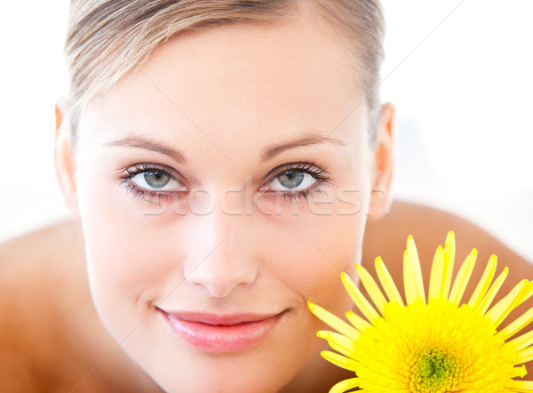 Close-up of a radiant woman lying on a massage table with a flower in a health spa Stock photo © wavebreak_media