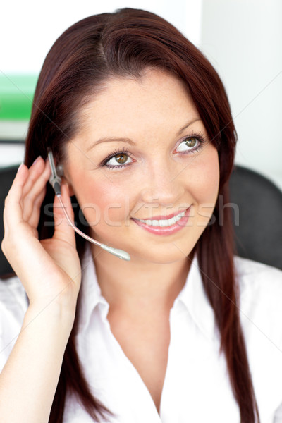 Serious young businesswoman with earpiece in a call center at her desk Stock photo © wavebreak_media