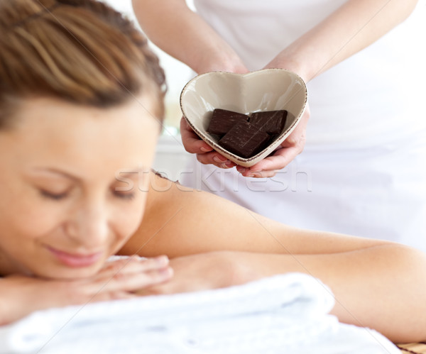 Relaxed woman lying on a massage table in a spa center with other woman holding a bowl in the shape  Stock photo © wavebreak_media