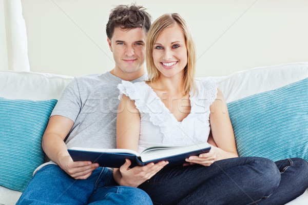 Cute couple reading a book together sitting on the couch at home and looking at the camera  Stock photo © wavebreak_media