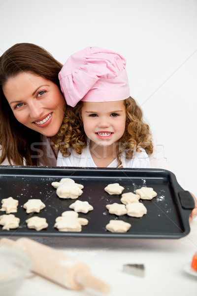 Happy mother and daughter holding a plate with biscuits in the kitchen Stock photo © wavebreak_media