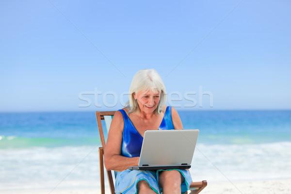 Woman working on her laptop on the beach Stock photo © wavebreak_media