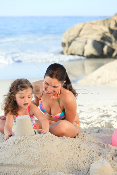 Daughter with her mother making a sand castle Stock photo © wavebreak_media