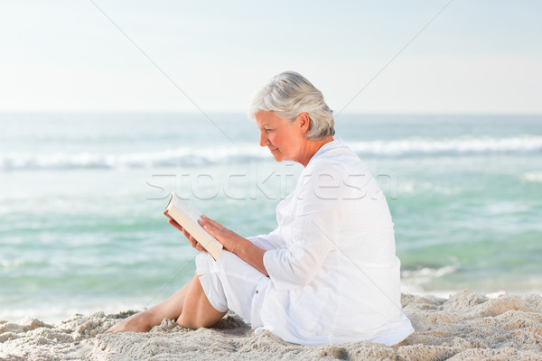 Elderly woman reading her book on the beach Stock photo © wavebreak_media