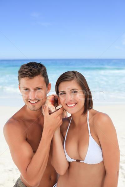 Amantes escuta concha mãos feliz fundo Foto stock © wavebreak_media