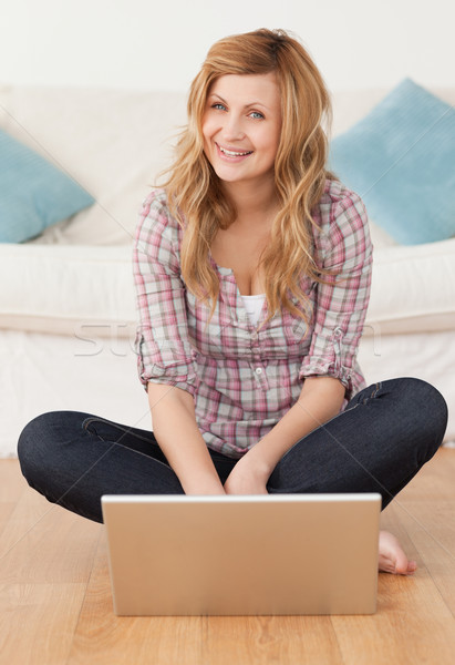 Smiling woman looking at the camera while surfing on her laptop in the living-room Stock photo © wavebreak_media