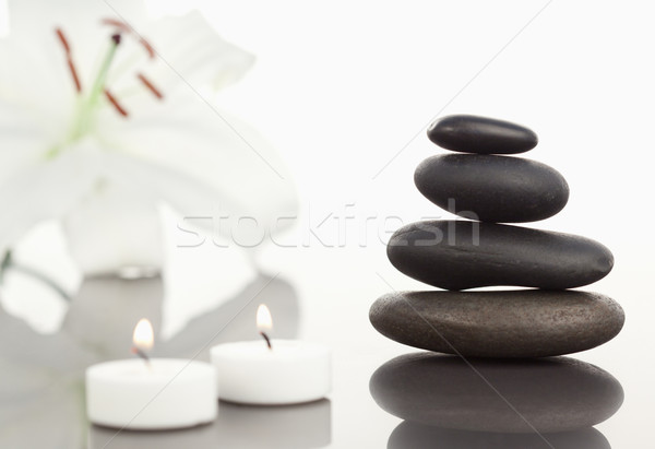 White orchid with lighted white candles and a black pebble stack the camera focus on the object Stock photo © wavebreak_media