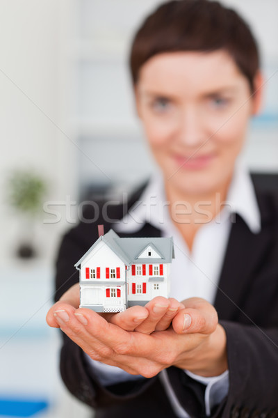 Portrait of a businesswoman holding a miniature house with the camera focus om the object Stock photo © wavebreak_media