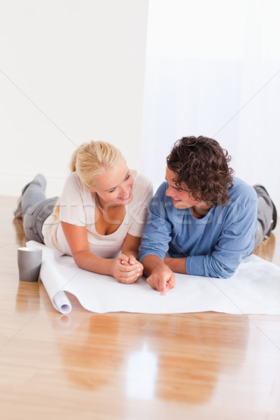 Portrait of a smiling couple organizing their new home while lying on the floor Stock photo © wavebreak_media