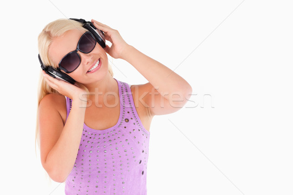 Glorious woman with earphones and sunglasses in a studio Stock photo © wavebreak_media