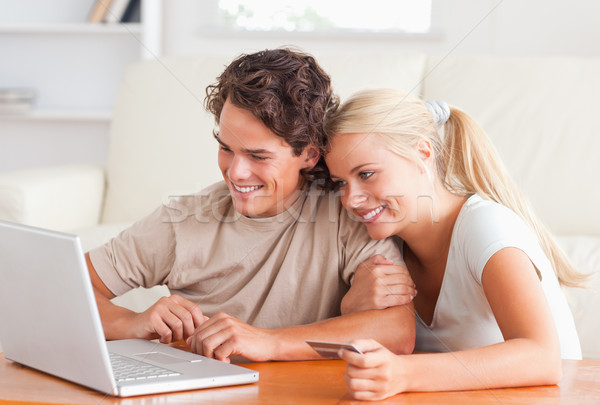 Cute couple with a laptop in their living room Stock photo © wavebreak_media