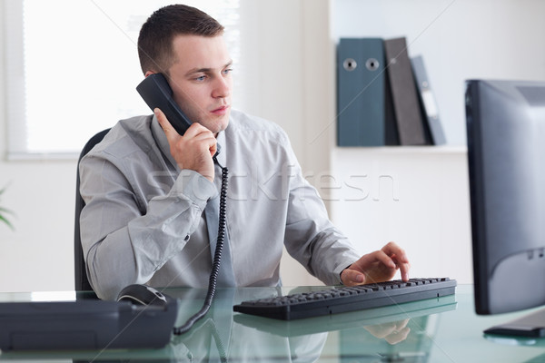 Concentrated businessman listening to caller while typing Stock photo © wavebreak_media