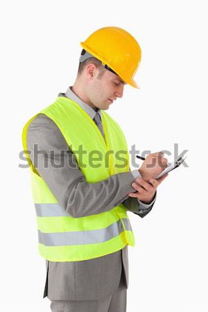 Smiling young construction worker taking notes against a white background Stock photo © wavebreak_media