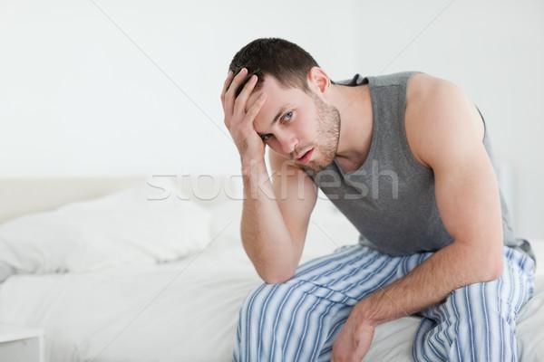 Junger Mann Sitzung Bett schauen Kamera Haus Stock foto © wavebreak_media