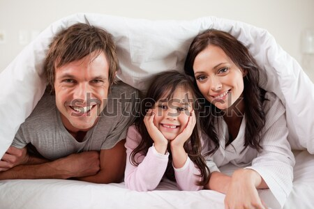 Parents lying under a duvet with their daughter in their bedroom Stock photo © wavebreak_media