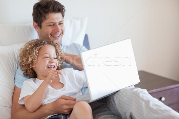 Stok fotoğraf: Baba · çocuk · dizüstü · bilgisayar · kullanıyorsanız · birlikte · yatak · Internet