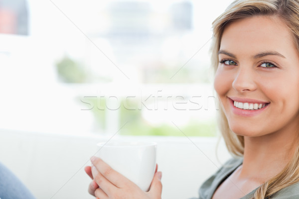 A woman holding a mug in her hands as she looks in front of her, smiling. Stock photo © wavebreak_media