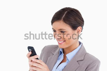 Close up of smiling female entrepreneur reading text message against a white background Stock photo © wavebreak_media