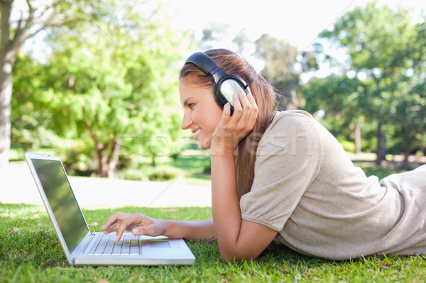 Side view of a woman with headphones and a laptop on the lawn Stock photo © wavebreak_media