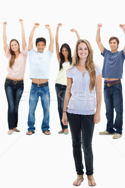 Woman smiling with people with their arms raised behind her against white background Stock photo © wavebreak_media