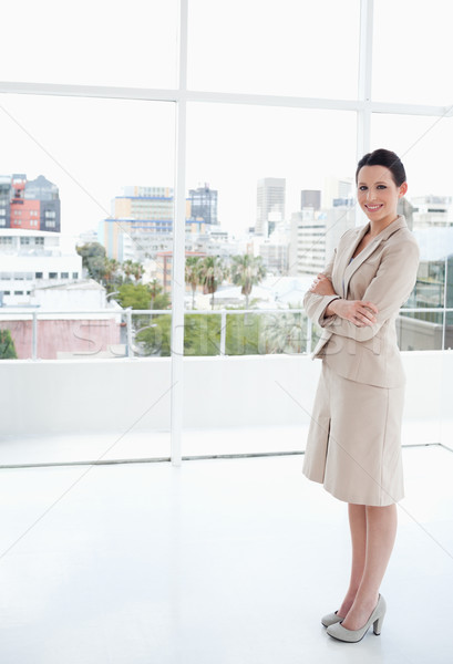 Smiling businesswoman standing upright in front of the bright window Stock photo © wavebreak_media