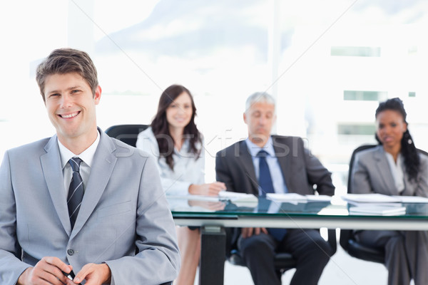 Smiling executive sitting in front of his earnest team and looking at the camera Stock photo © wavebreak_media