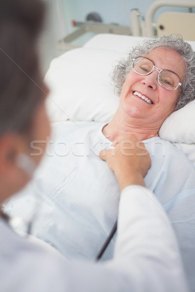 Elderly patient smiling to a doctor in hospital ward Stock photo © wavebreak_media