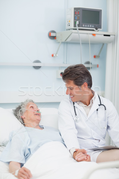Doctor looking at a patient while taking her hand in hospital ward Stock photo © wavebreak_media