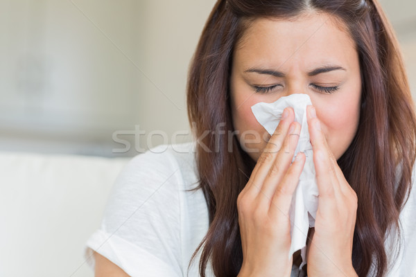 Burnette woman blowing nose into tissue Stock photo © wavebreak_media