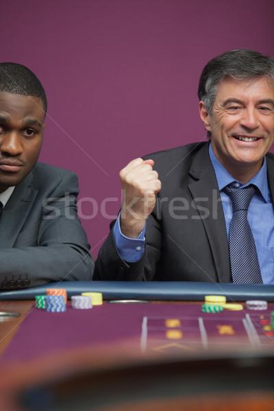 Mosolyog férfi ül asztal kaszinó ünnepel Stock fotó © wavebreak_media
